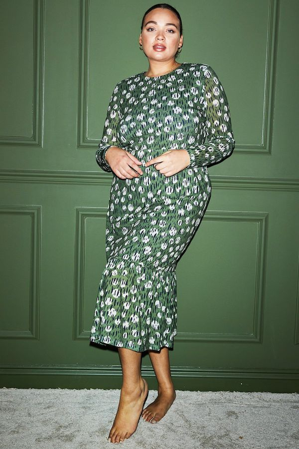 A plus-size model wearing a green midi dress.