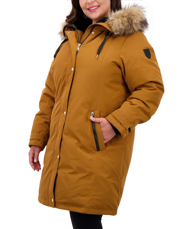 A plus-size model from Macy's wearing a mustard yellow coat with faux fur hood.