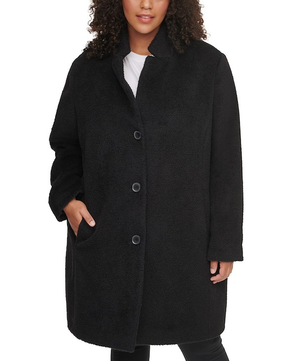 A plus-size model from Macy's wearing a black single-breasted coat.