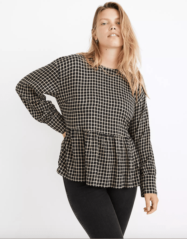 A plus-size model wearing a black and white peplum blouse from Madewell.