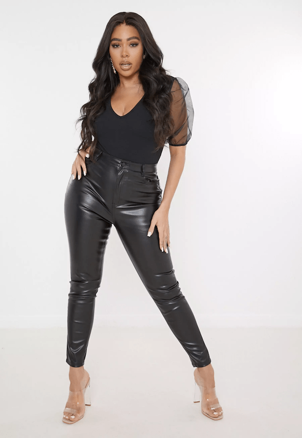 A plus-size model for Missguided wearing leather trousers.