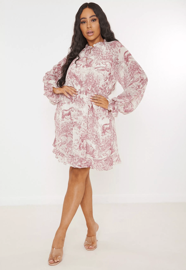 A plus-size model for Missguided wearing a pink printed wrap dress.