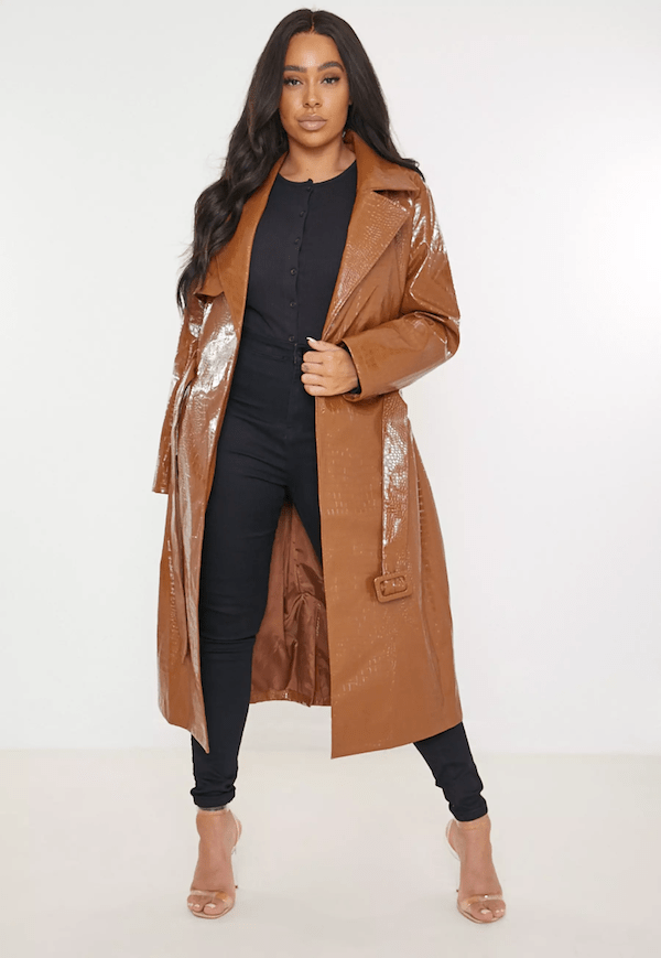 A plus-size model for Missguided wearing a faux leather trench coat.