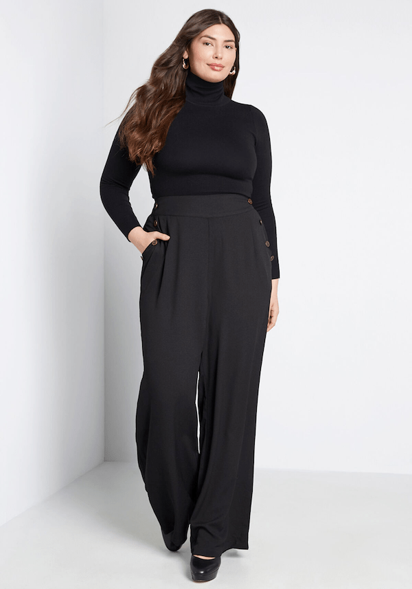 A plus-size model from ModCloth wearing dark gray trousers.