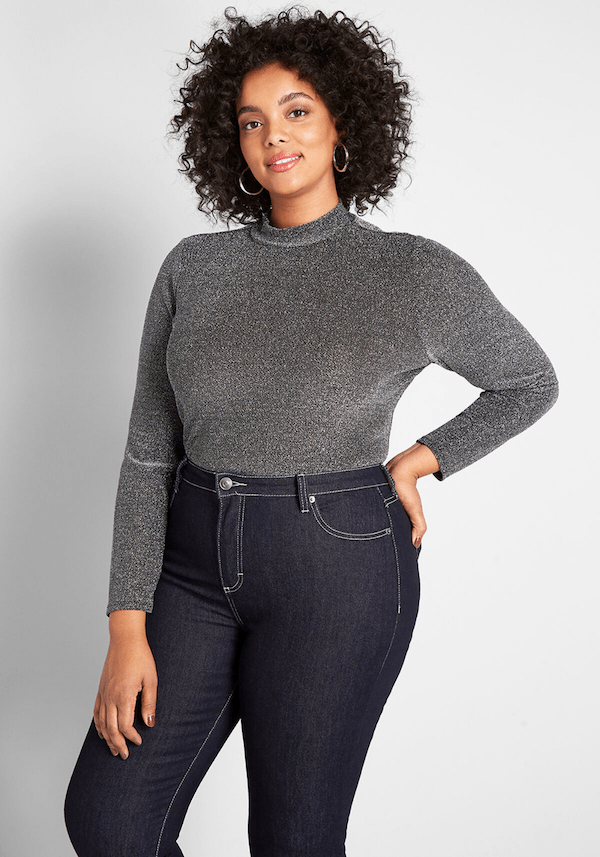 A plus-size model from ModCloth wearing a shimmery silver top.