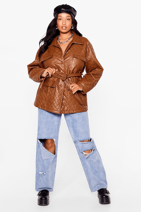 A plus-size model from Nasty Gal wearing a brown faux leather jacket.