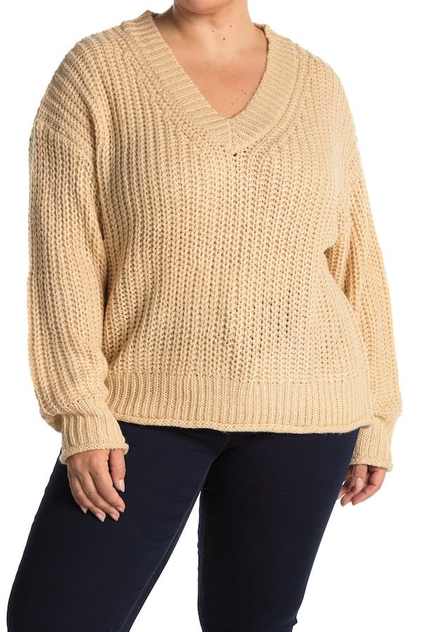 A plus-size model from Nordstrom Rack wearing a tan v-neck sweater.