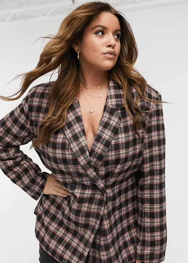 A plus-size model wearing a plaid blazer, which is currently marked down at ASOS's 2020 Black Friday sale.