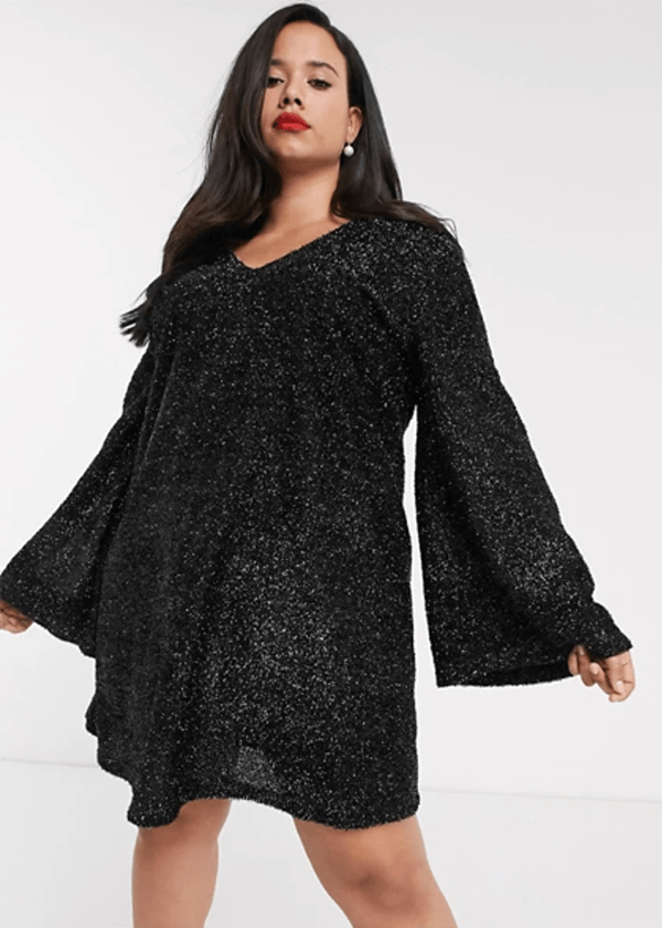 A plus-size model wearing a black sequin dress, which is currently marked down at ASOS's 2020 Black Friday sale.