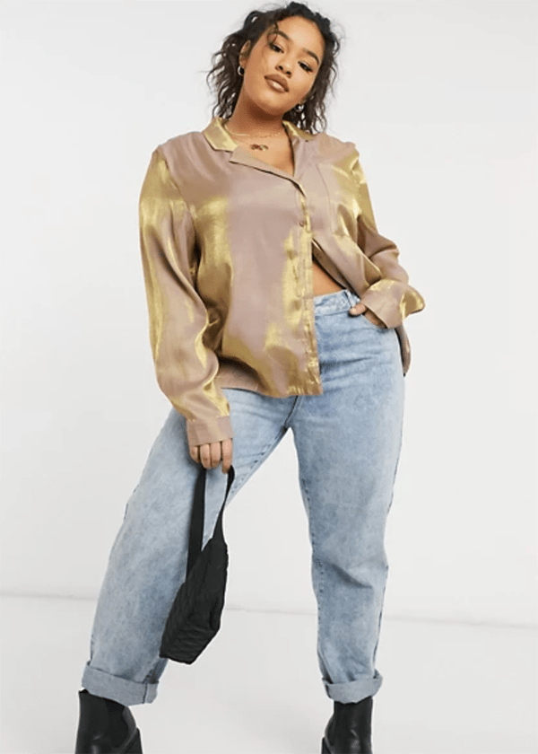 A plus-size model wearing a gold button-up blouse, which is currently marked down at ASOS's 2020 Black Friday sale.