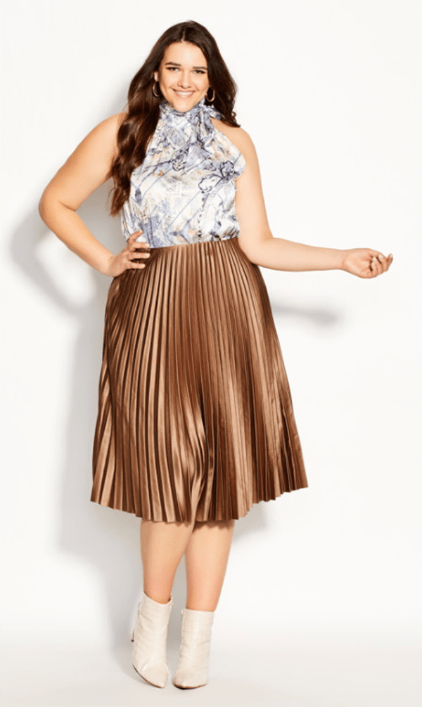 A plus-size model wearing a gold pleated midi skirt, which will be marked down at City Chic's 2020 Black Friday sale.