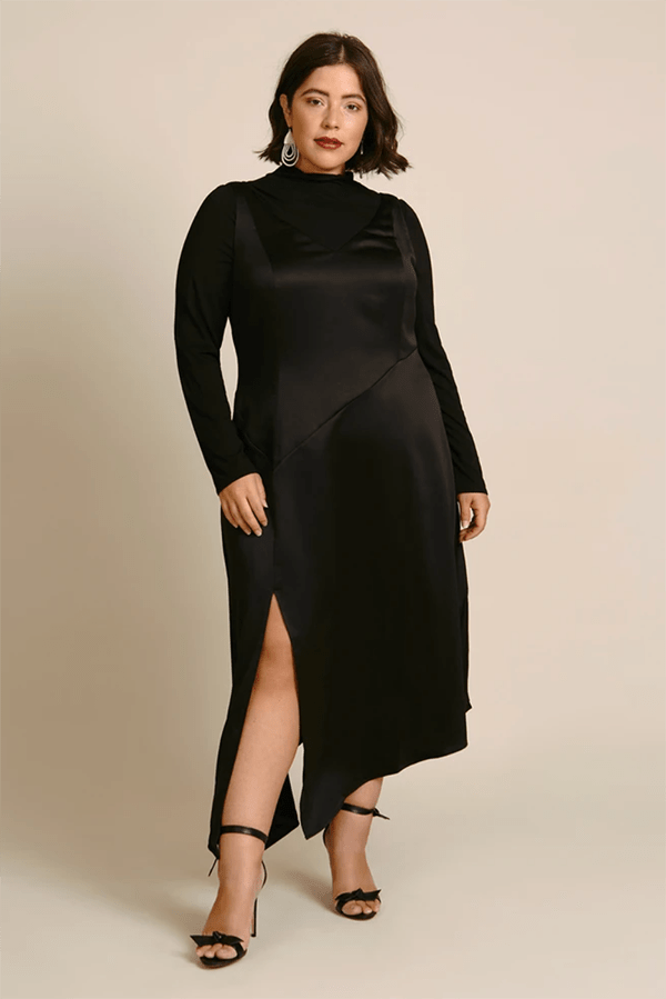 A plus-size model wearing a black dress, which is currently marked down at 11 Honore's 2020 Black Friday sale.