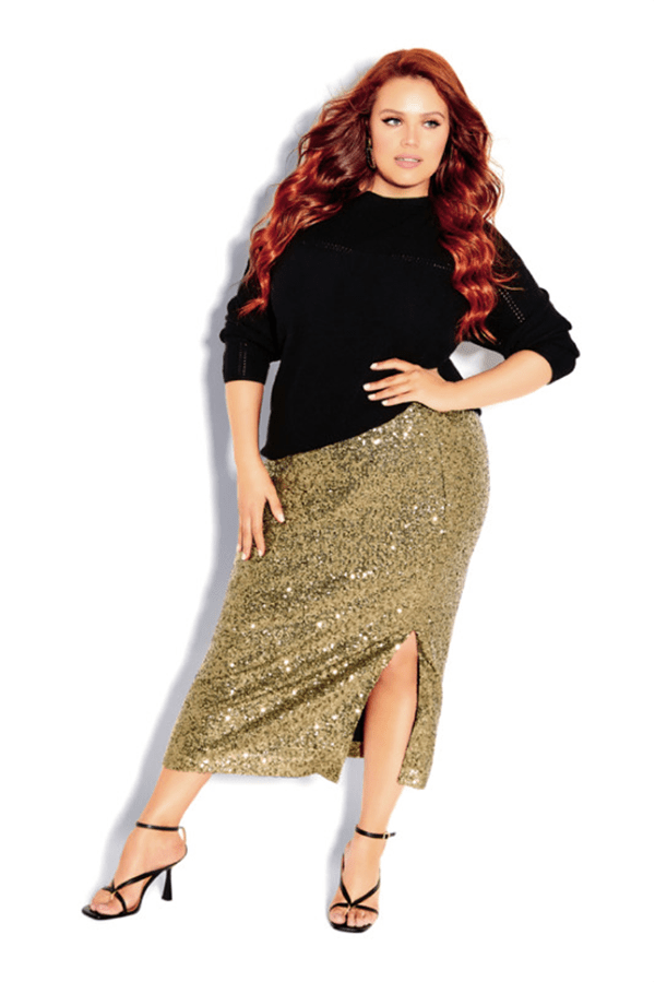 A plus-size model wearing a gold sequin midi skirt, which is currently marked down at CoEdition's 2020 Black Friday sale.