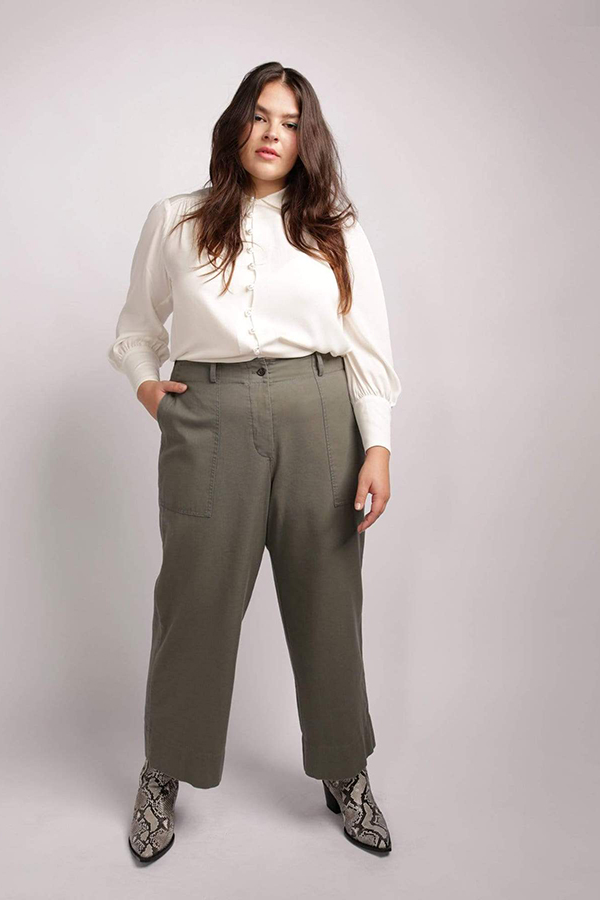 A plus-size model wearing a pair of olive trousers, which are currently marked down at CoEdition's 2020 Black Friday sale.