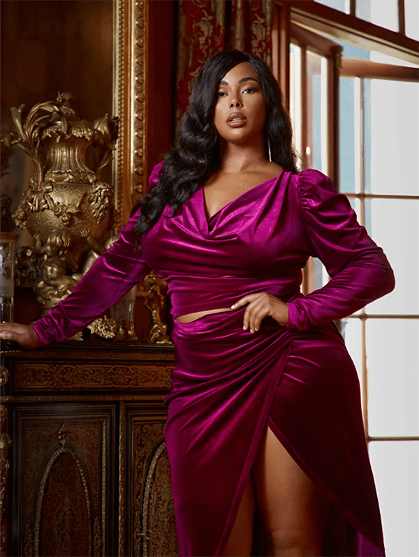 A plus-size model wearing a fuchsia velvet top, which will be marked down at Fashion to Figure's 2020 Black Friday sale.