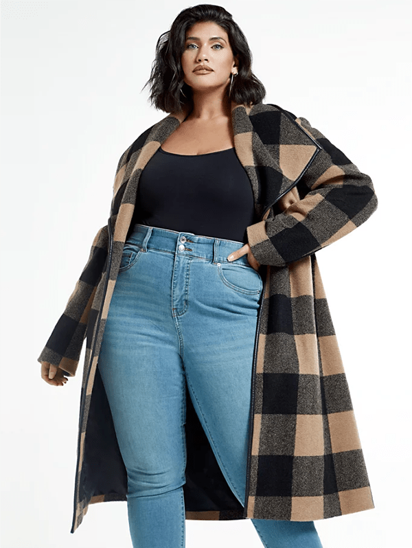 A plus-size model wearing a checked trench coat, which will be marked down at Fashion to Figure's 2020 Black Friday sale.