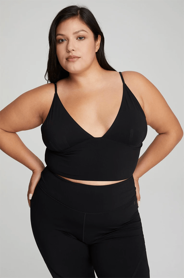 A plus-size model wearing a black tank top, which will be marked down at Good American's 2020 Black Friday sale.