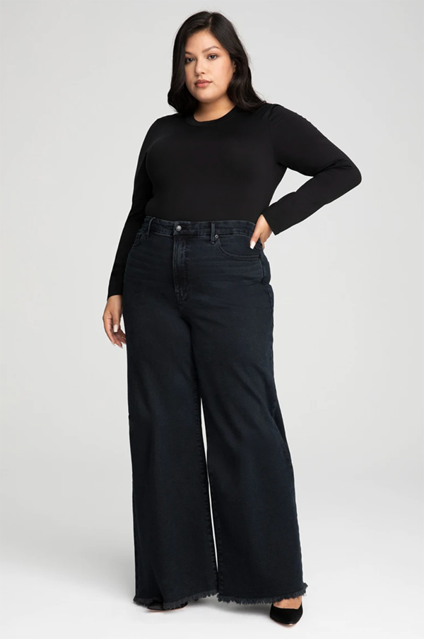 A plus-size model wearing wide-leg black jeans, which will be marked down at Good American's 2020 Black Friday sale.