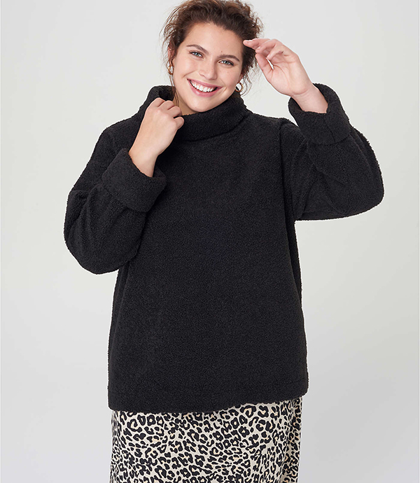 A plus-size model wearing a black turtleneck sweater, which will be marked down at Loft's 2020 Black Friday sale.