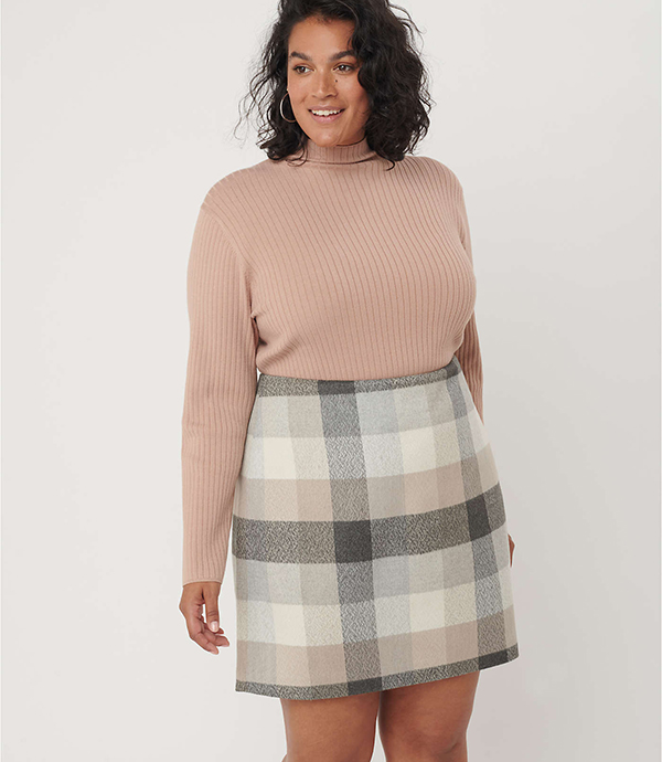 A plus-size model wearing a plaid mini skirt, which will be marked down at Loft's 2020 Black Friday sale.