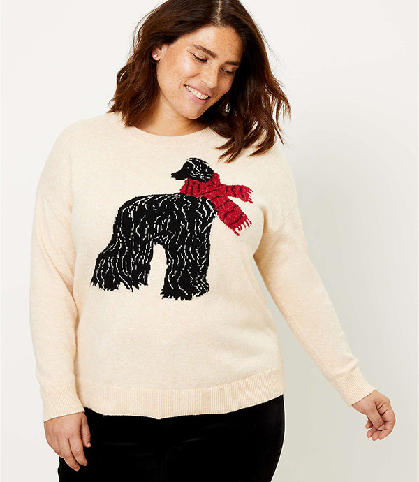 A plus-size model wearing a kitschy sweater, which will be marked down at Loft's 2020 Black Friday sale.