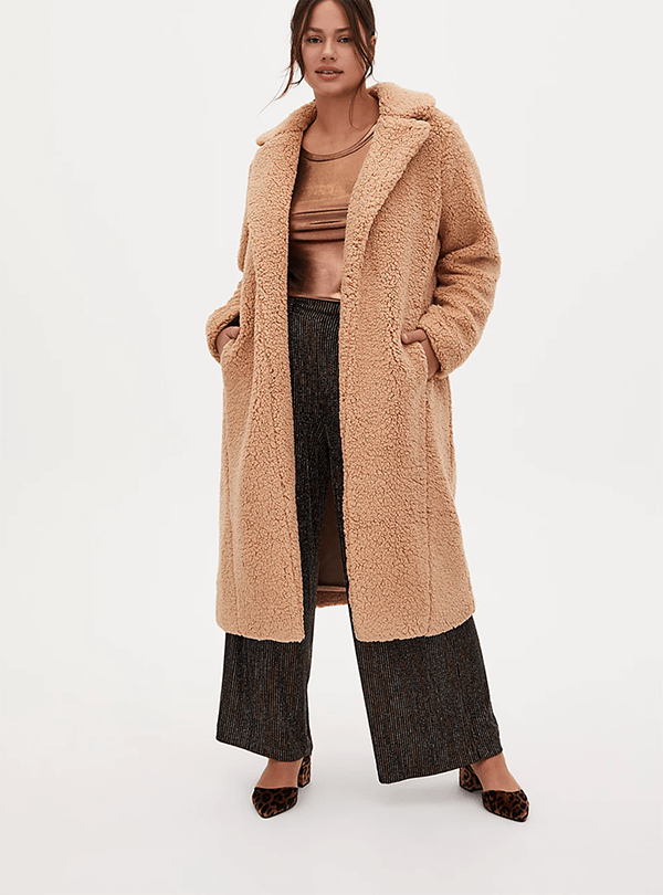 A plus-size model wearing a tan teddy coat, which will be marked down at Torrid's 2020 Black Friday sale.