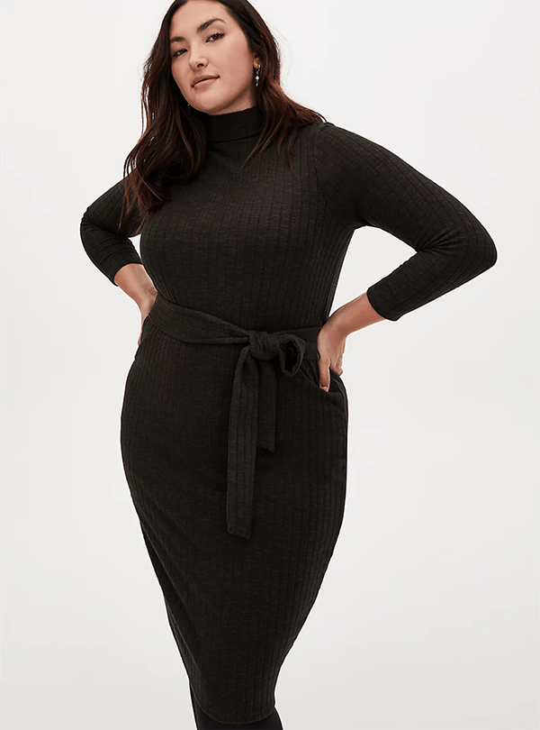 A plus-size model wearing an olive ribbed midi dress, which will be marked down at Torrid's 2020 Black Friday sale.