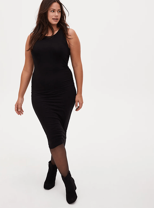 A plus-size model wearing a black ribbed midi dress, which will be marked down at Torrid's 2020 Black Friday sale.