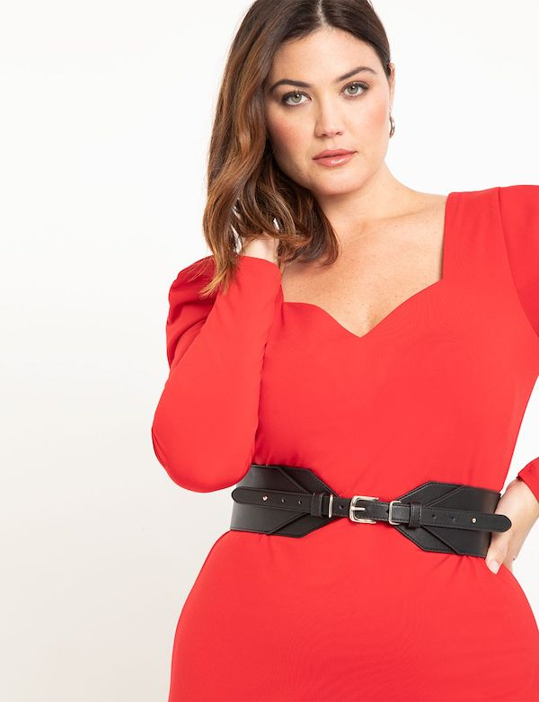 A plus-size model wearing a black buckled corset belt.
