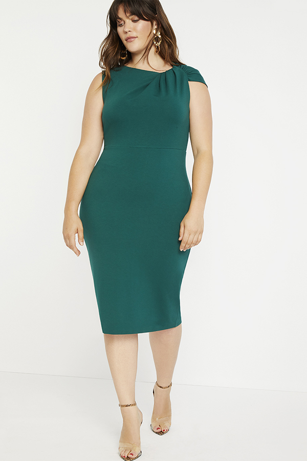A plus size model wearing a green fitted midi dress.
