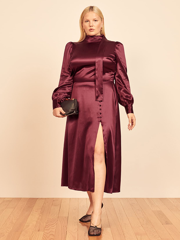 A plus-size model wearing a burgundy holiday dress from Reformation.