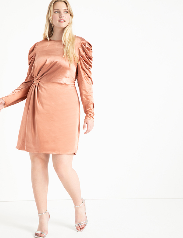 A plus-size model wearing a gold satin holiday dress from Eloquii.