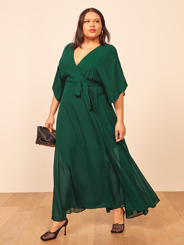 A plus-size model wearing an emerald green holiday dress from Reformation.