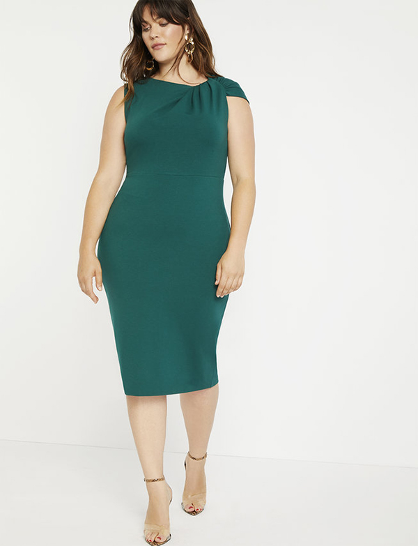 A plus-size model wearing an emerald green holiday dress from Eloquii.