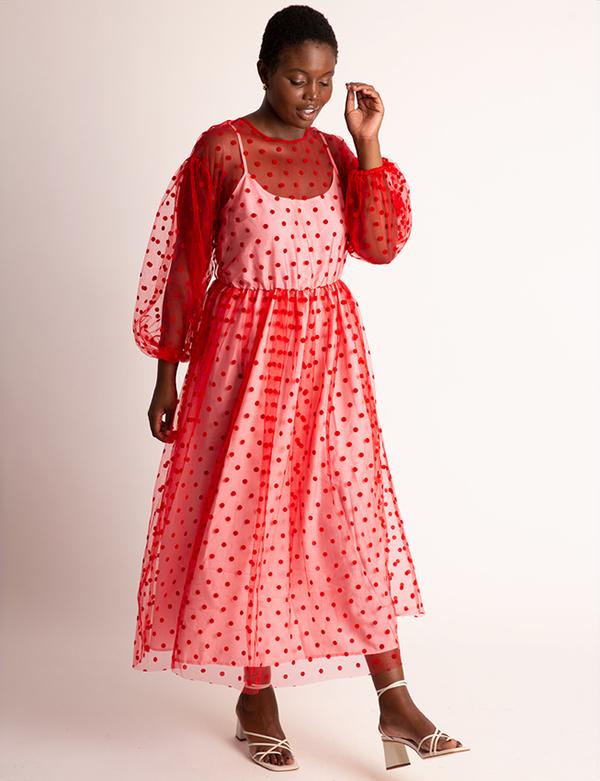 A plus-size model wearing a red polka dot holiday dress from Eloquii.