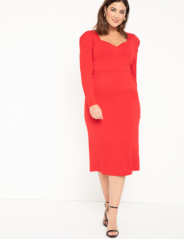 A plus-size model wearing a red holiday dress from Eloquii.