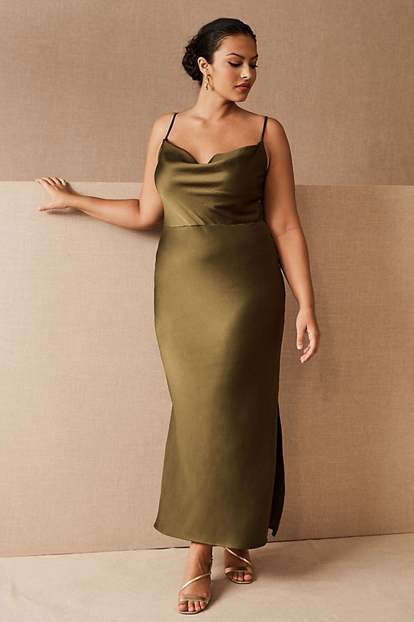 A plus-size model wearing an olive green slip dress from Anthropologie.