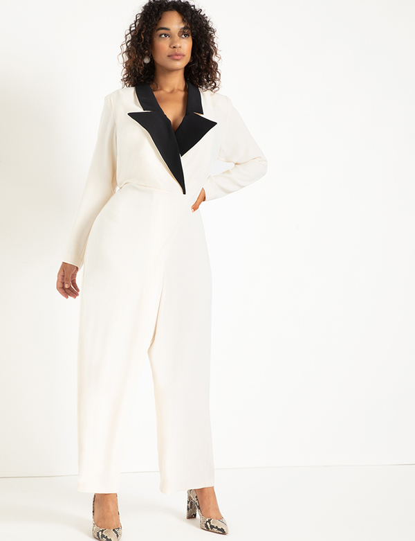 A plus-size model wearing a white tuxedo holiday jumpsuit from Eloquii.