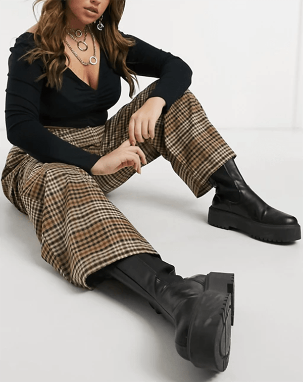 A plus-size model wearing a pair of brown plaid pants.