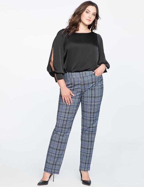 A plus-size model wearing a pair of blue plaid pants.