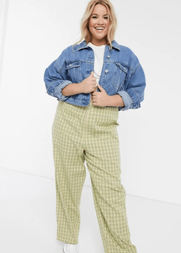 A plus-size model wearing a pair of light green, wide-leg plaid pants.