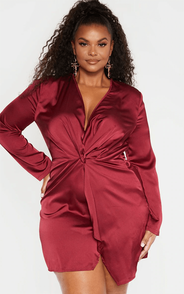 A plus-size model wearing a dark red satin wrap dress.