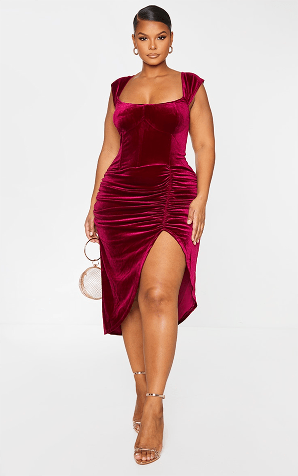 A plus-size model wearing a dark red velvet midi dress.