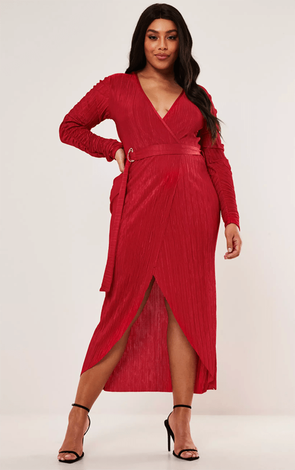 A plus-size model wearing a red wrap midi dress.