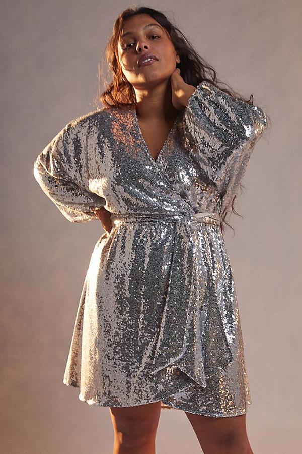 A plus-size model wearing a silver sequin wrap dress.