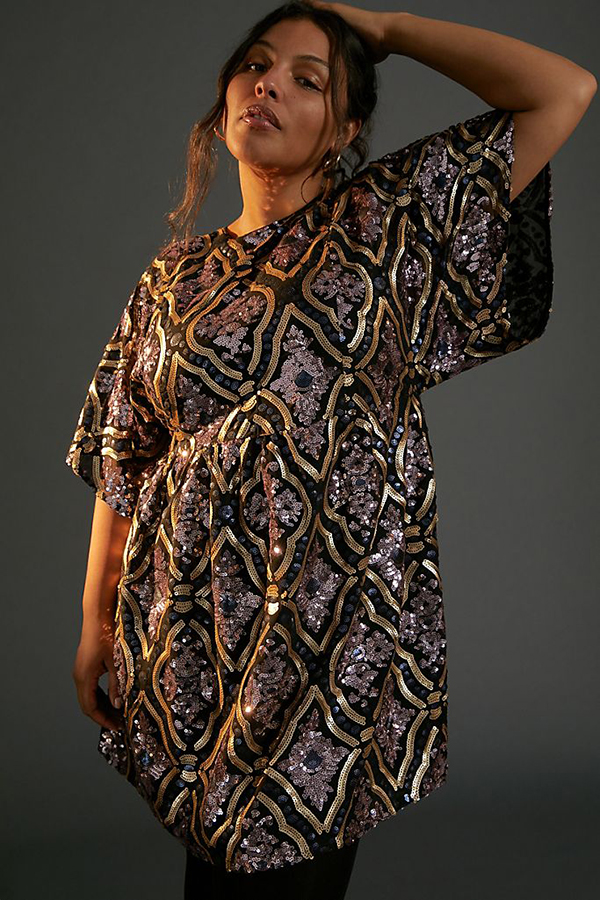 A plus-size model wearing a printed sequin dress.