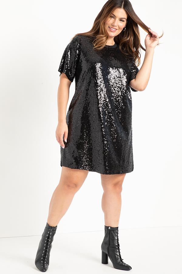 A plus-size model wearing a black sequin shift dress.