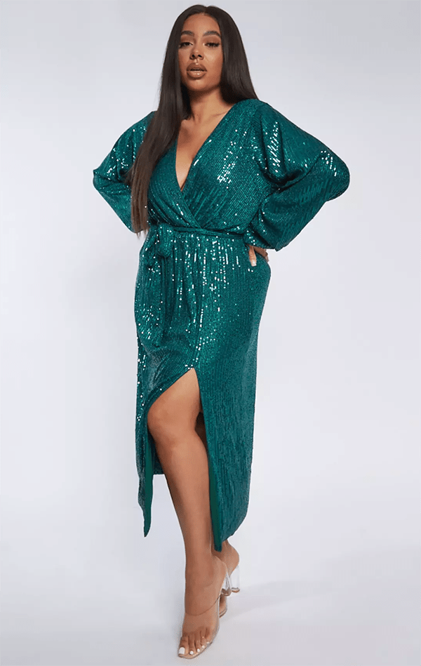 A plus-size model wearing a teal sequin wrap dress.