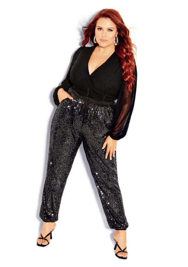 A plus-size model wearing a pair of charcoal sequin joggers.