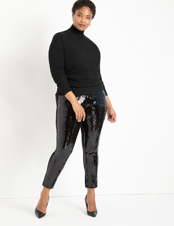 A plus-size model wearing a pair of black sequin skinny pants.